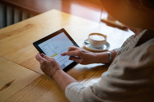 Senior woman holding tablet. Wooden table and coffee cup. Buy licensed apps.