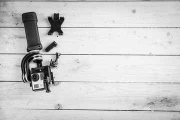 Action camera on the wooden table with a stabilizer and other accessories