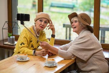 Elderly women taking selfie. Two senior ladies in cafe. Testing new monopod.