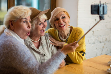 Three women taking selfie. Senior ladies indoor. Save friendship after many years.