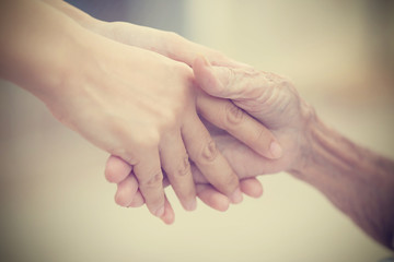 Old and young holding hands on light background, vintage tone.