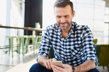 Man smiling using smartphone