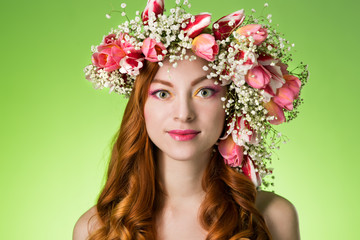 eyed redhead girl with bright makeup and a wreath of spring flow