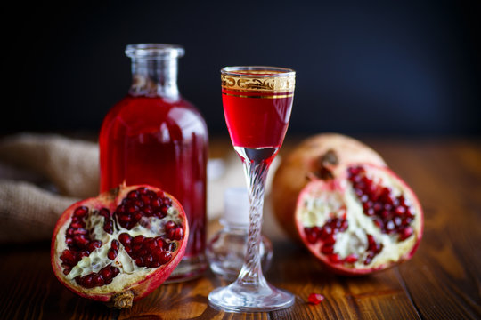 sweet pomegranate alcoholic cordial in the decanter with a glass