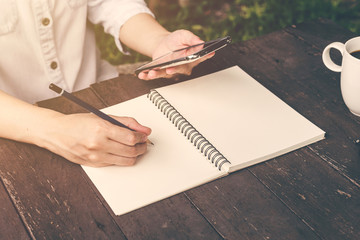 close up hand woman writing notebook and holding phone on wood t
