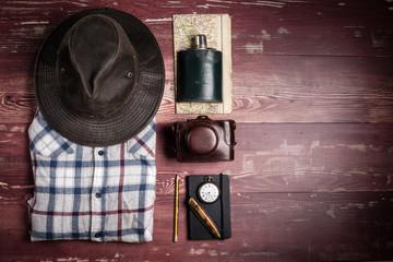Des accessoires de randonnée  avec chemise à carreaux et chapeau sur des planches en bois