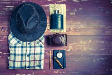 Des accessoires de randonnée  avec chemise et chapeau sur des planches en bois en filtre vintage