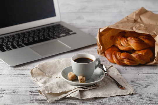 Fresh pastry and cup of brew coffee on table in office with lapt