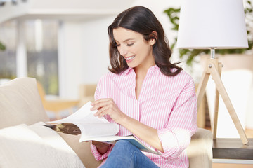 Enjoy relaxing at home. Happy young woman enjoy to reading a magazine while relaxing at home.