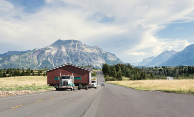 horizontal image of a big transport truck moving a large home along a narrow highway with mountains looming in the background in the summer time. Wall mural