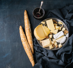 Cheese plate. Assortment variety of cheese with walnuts, jam and bread on vintage metal plate with textile over dark blue canvas as background. Top view with space. Appetizer theme