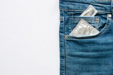 blue jeans with condom in pocket on a white background with space for text