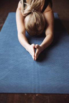 Closeup of sportswoman practicing yoga on mat