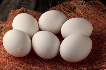 Raw fresh white farmer's eggs on decorative straw and wooden background. Healthy and sport food. Easter day theme.