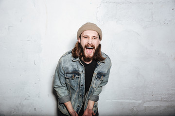 Screaming bearded hipster man posing over wall background.