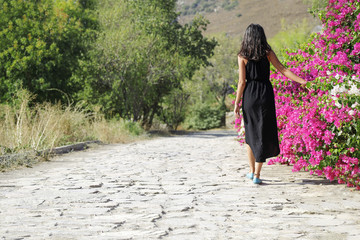 The woman touching bougainvillea on the wall.