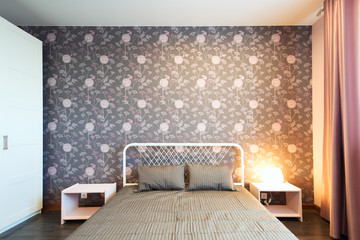 Interior bedroom with a large double bed with bedside tables on a background of modern wallpaper