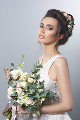 Spring beauty portrait of sexy bride's hairstyle with a wreath and a bouquet in hands isolated on a gray background.