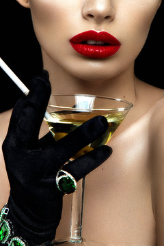 Fashion woman portrait of half face. Red lips and hand with martini and cigarette.