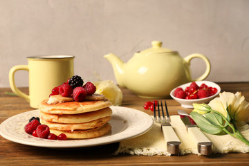 Stack of fresh pancakes with fruits on plate