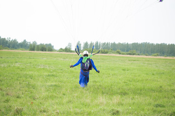 A skydiver landed on a green field
