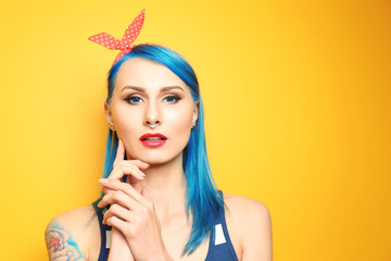 Beautiful young woman with stylish color hair and tattoo on yellow background
