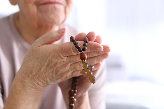 Elderly woman with rosary beads at home, closeup