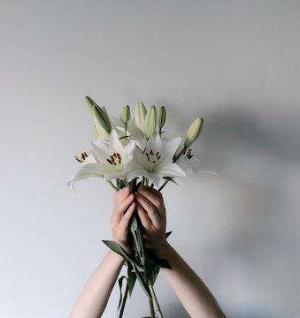 Frau hält mehrere Lilien hoch