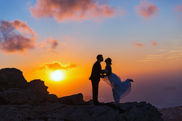Silhouette of bride and groom on  sea sunset