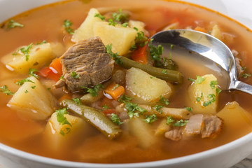Bowl of vegetable beef soup with spoon