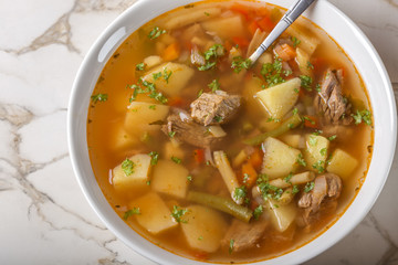 Bowl of vegetable beef soup and spoon