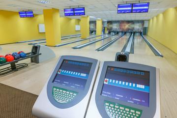 Bowling balls return machine, alley background