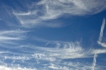 White clouds whisp across a beautiful clear blue sky