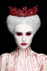 Mysterious beauty portrait of snow queen covered with blood. Bright luxury makeup. Black demon eyes.
