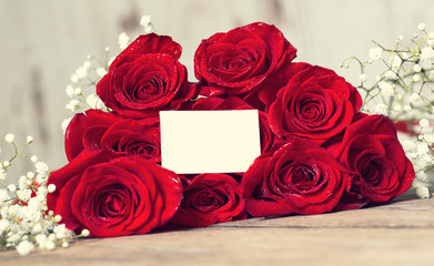 Bouquet of red roses on wooden table.