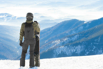 Young snowboarder standing next to snowboard thrusted into snow and looking at a beautiful mountain scenery