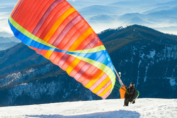 Photo sur Aluminium Aerien Paraglider launching into air from the very top of a snowy mountain slope