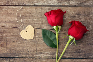 Red roses and heart on wooden background.