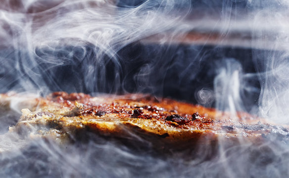 smoke and steam rise from a pork steak on grill pan