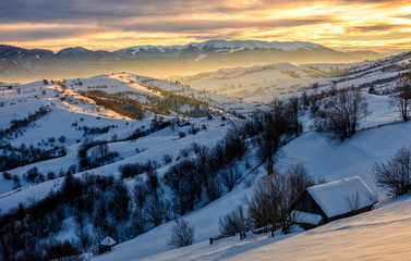 winter landscape in mountainous rural area at sunrise