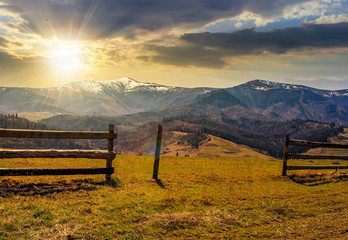 fence on rural field in spring at sunset