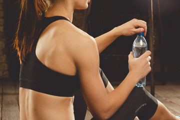 Beautiful athletic woman drinking water after workout at home