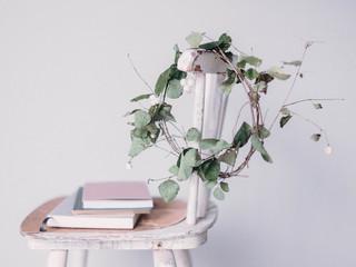 selbstgemachter kranz hängt an lehne eines vintage stuhls