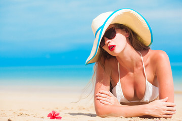 portrait of young beautiful woman on beach with red lips and hibiscus in straw hat