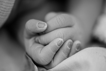 Newborn baby hands clasped together darkened skin from just being born slowly changing colour caucasian female daughter golden hour of life maternity photoshoot in black and white