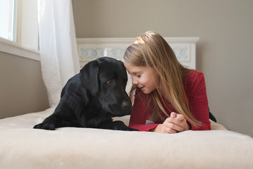 Little girl and her dog on the bed.