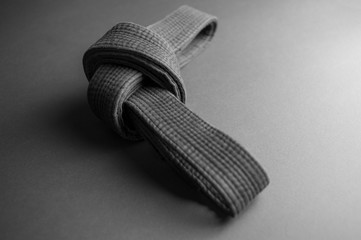 Black judo belt tied in a knot isolated on black background