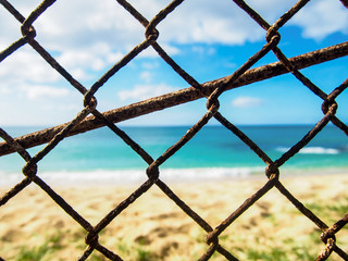 Closeup photo of a rusty old chain link fence with a beach in the background near Makaha Hawaii.