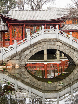 A traditional Chinese bridge reflects in a calm pond in a memorial park in the old city of Dali China.