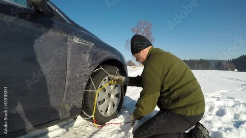 A man fitting snow chains  The man put snow chains on the